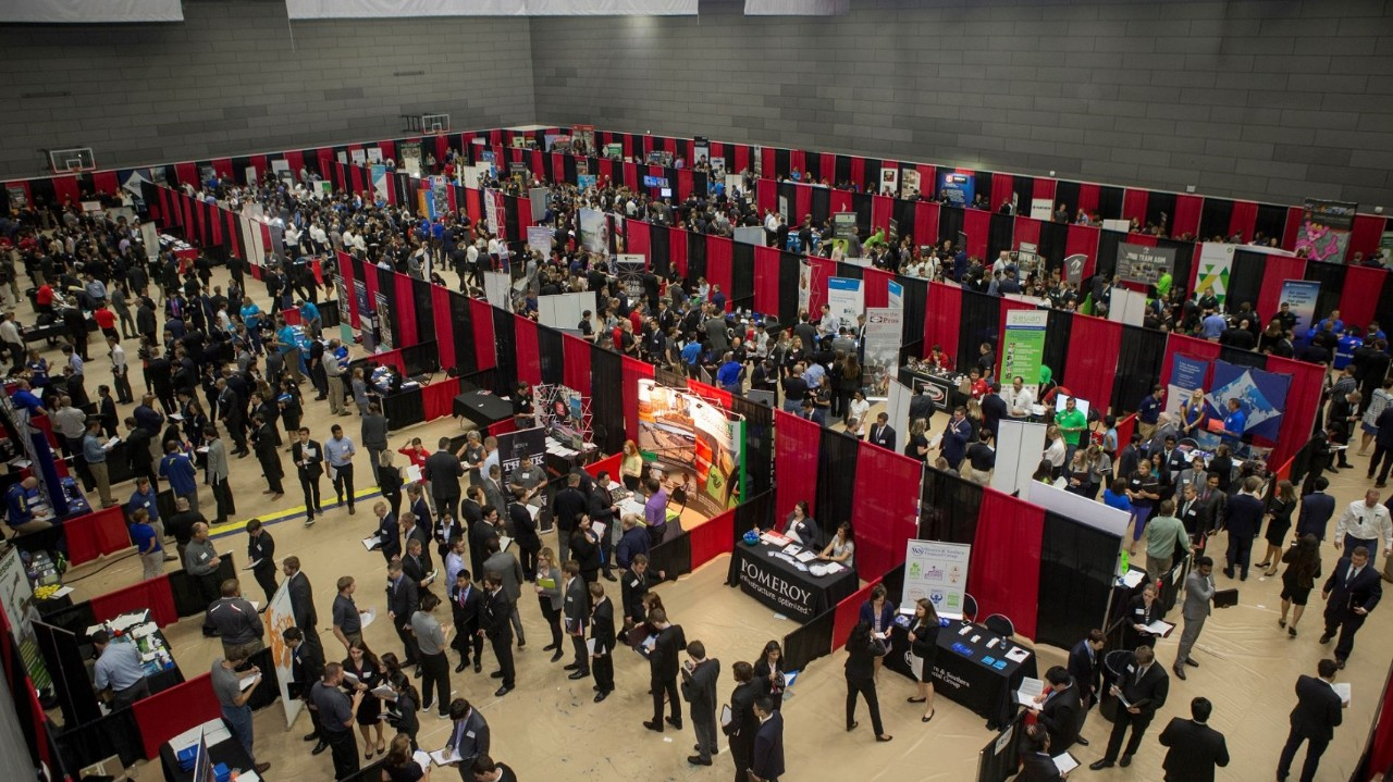 Overhead view of students in suits browsing tables on the floor of the UC Campus Recreation Center
