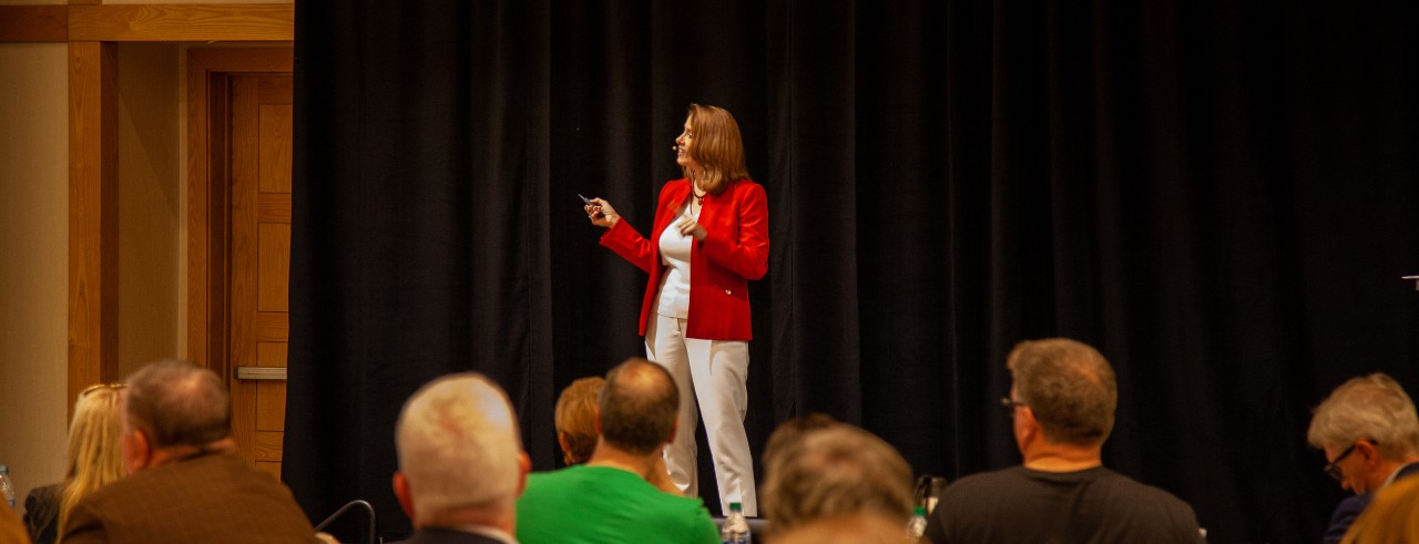 Sonya Hall speaking at event in red business jacket in front of audience.