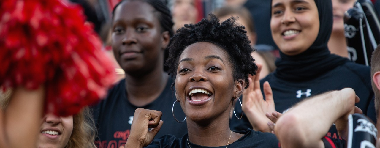 UC students celebrate during a UC football game.