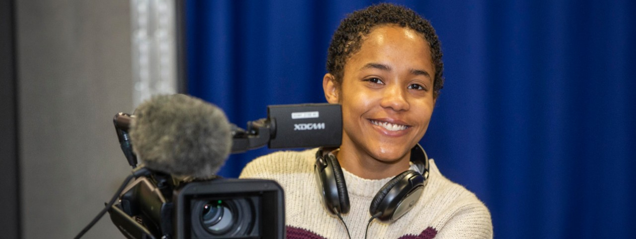 UC electronic media student Mary Williams with headphones on and operating a large video camera.