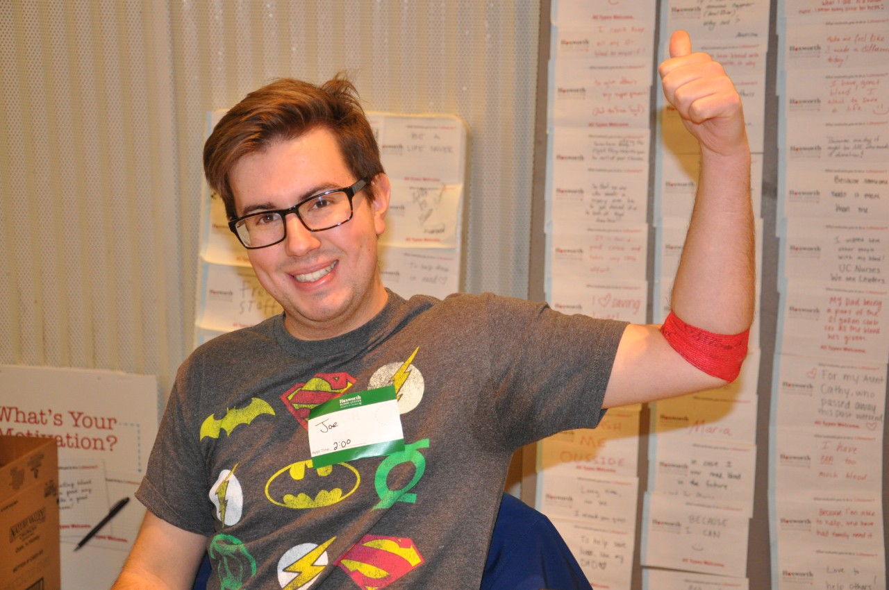 Donor at UC Blood Drive showing off red arm bandage after donating
