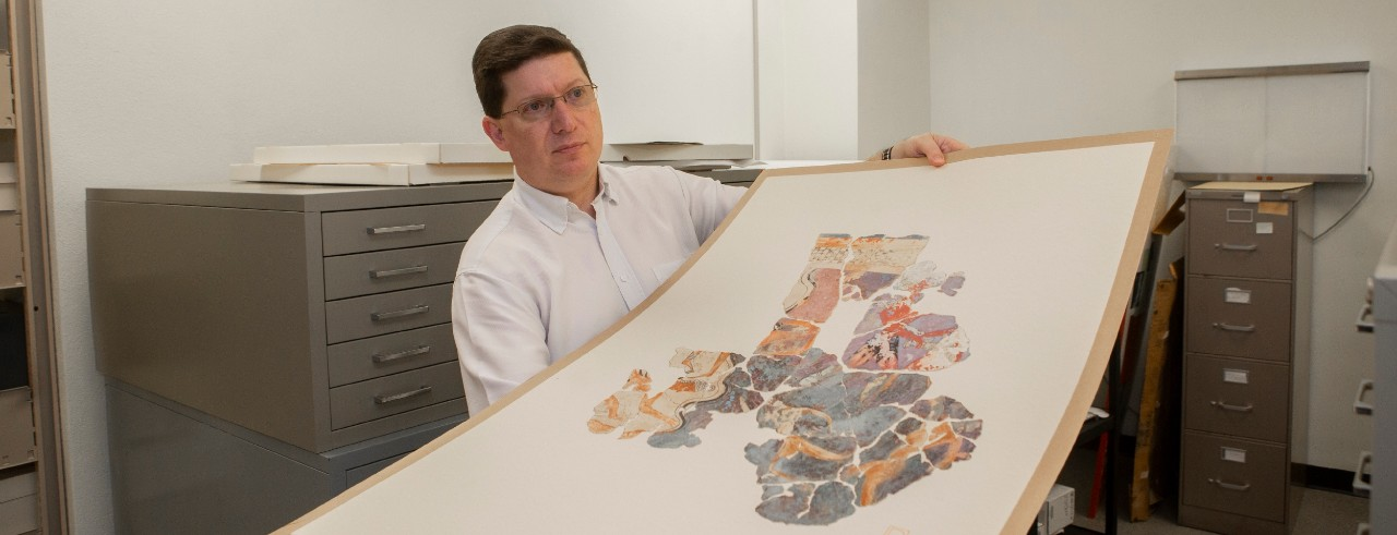 UC Classics archivist Jeff Kramer pulls out an original pottery painting commissioned during an excavation of Troy.