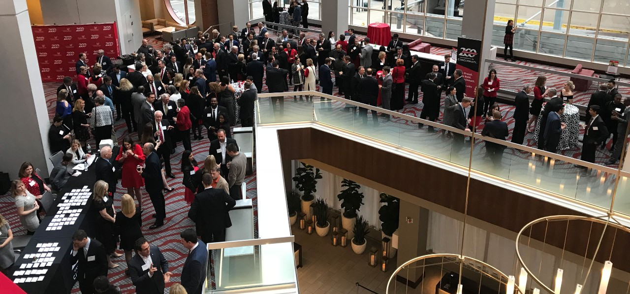 a crowd of approximately 100 people gather and mingle in an atrium for a reception