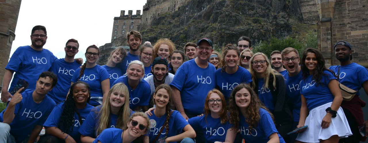 Students in Richard Hess's study abroad program take a group photo in front of a Scottish castle.