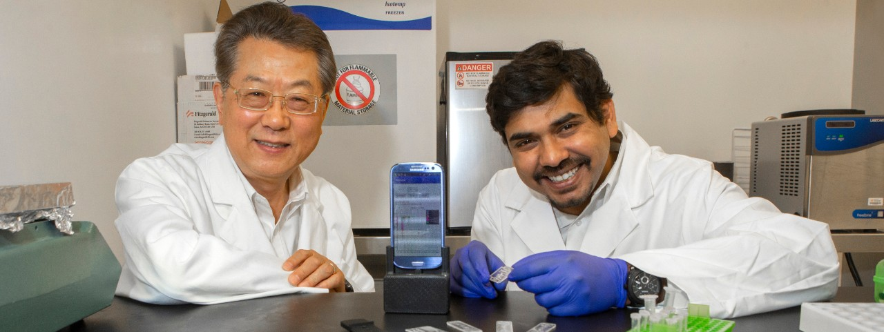 UC engineering professor Chong Ahn, left, and his graduate student Sthitodhi Ghosh pose with the lab accessory they designed for smartphones.