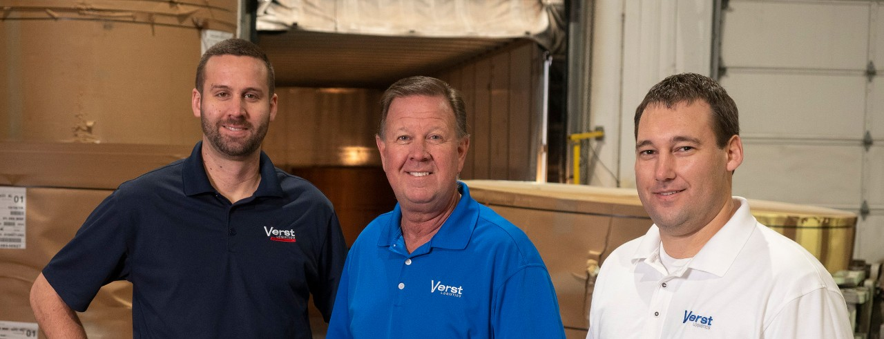 From left: Chris Verst, Paul Verst and Kyle Stadtmiller posing at Verst Logistics plant floor.