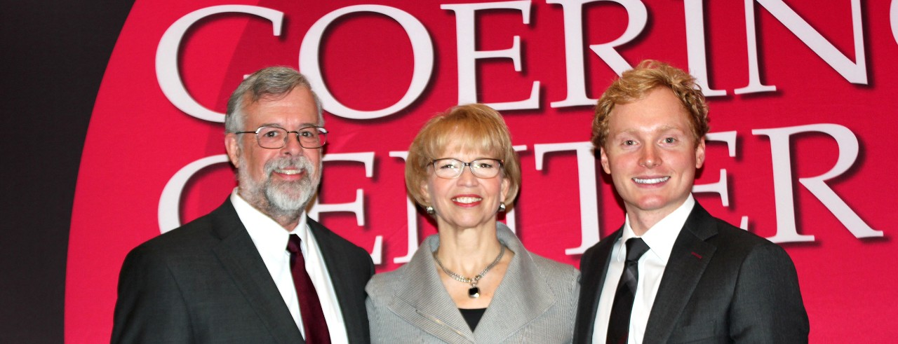 "Photo of Alan Beaulieu and Connor Lokar of ITR Economics with Carol Butler of the Goering Center, posing in front of red ""Goering Center"" backdrop."