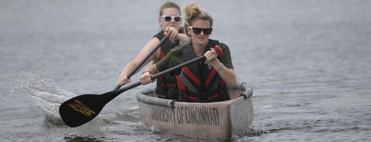 UC students race their concrete canoe on a lake as part of a civil engineering competition.