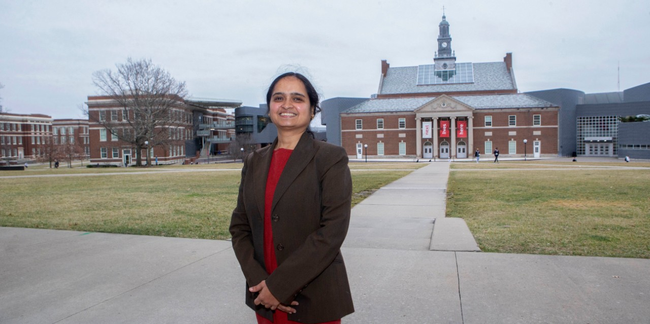 Shailaja Paik standing on campus with the Next Lives Here sign behind her
