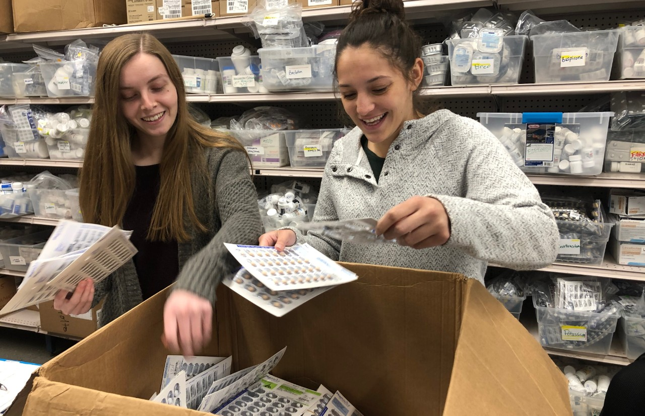 Two female students look through the contents of a cardboard box