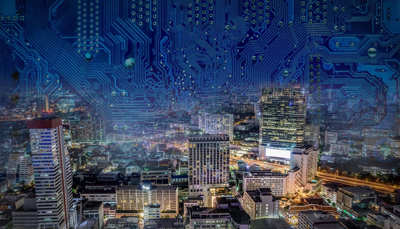 A colorful nighttime view of an urban area with circuitboard patterns overlaid