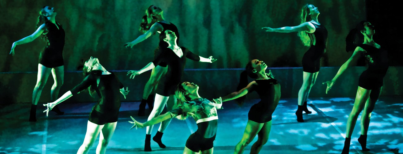 CCM student dancers perform on stage with dramatic lighting