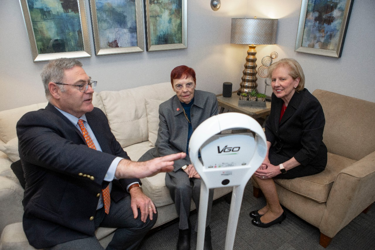 A man and two women are sitting on a couch and a chair looking at a telehealth robot.