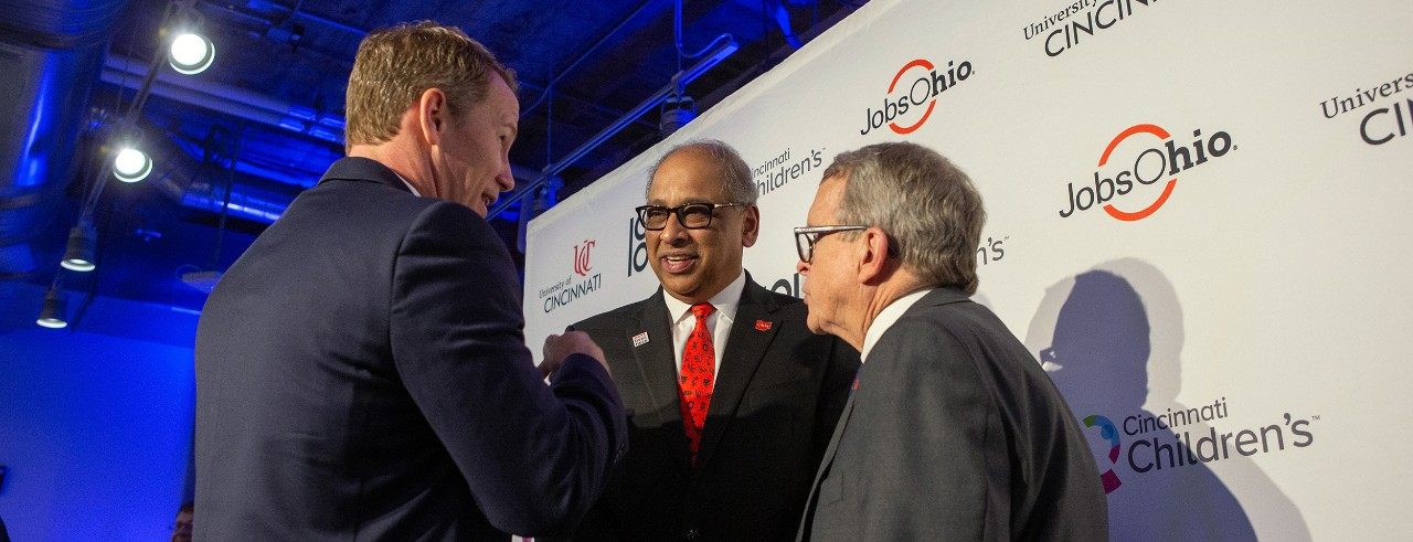 Lt. Gov. Jon Husted, UC President Neville Pinto and Ohio Gov. Mike DeWine on the podium at the 1819 Innovation Hub