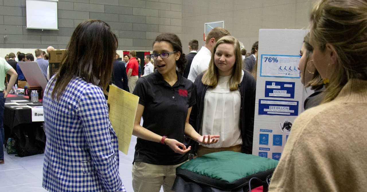 Four young women on a student team present an elevator pitch for a product to a judge in a science-fair-like setting in a gymnasium
