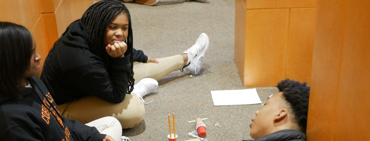 Three middle school students sit on the floor, building with pencils, plastic cups and cardboard.