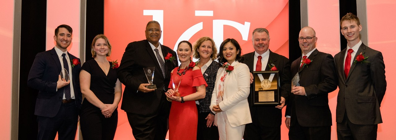 Eight awardees in business professional apparel stand with the dean of the Lindner College of Business, center on a stage in front of a UC backdrop
