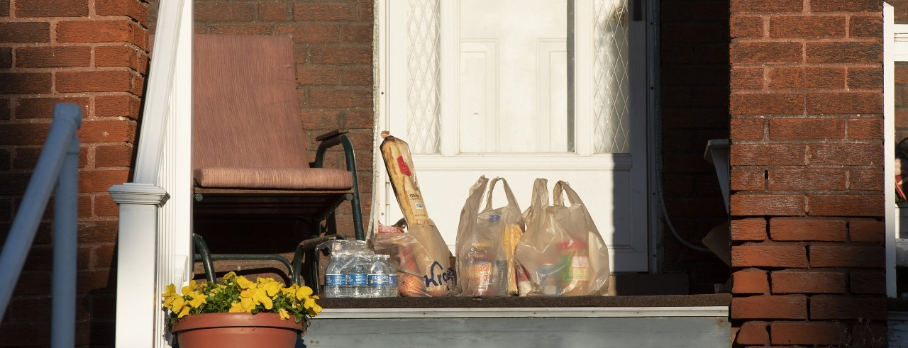three bags of Kroger groceries on front porch of a home