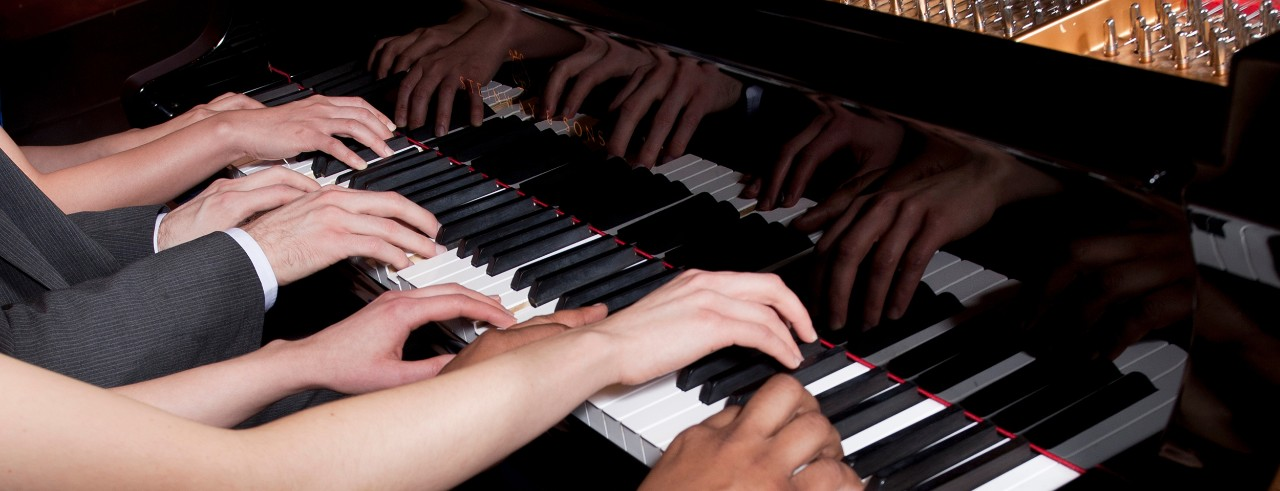 A close shot of multiple hands on a piano keyboard.