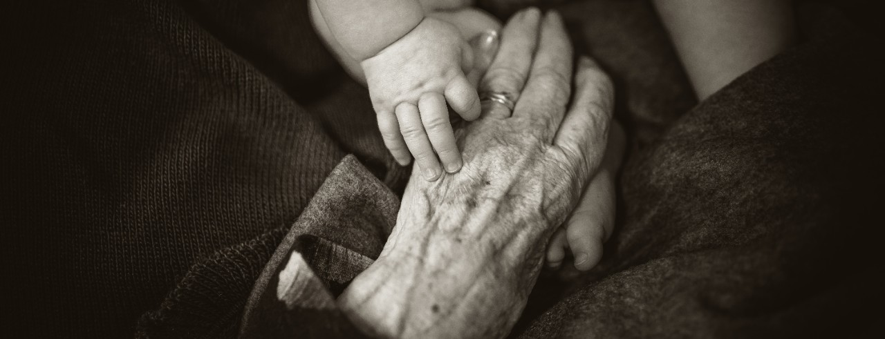 Senior citizen and baby holding hands