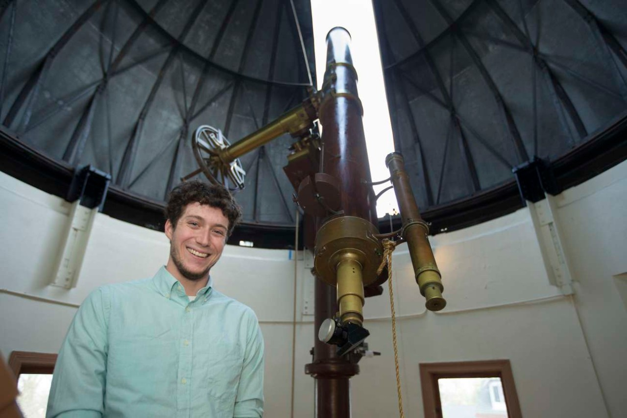 Kevin Wagner poses in front of a historic telescope at the Cincinnati Observatory.
