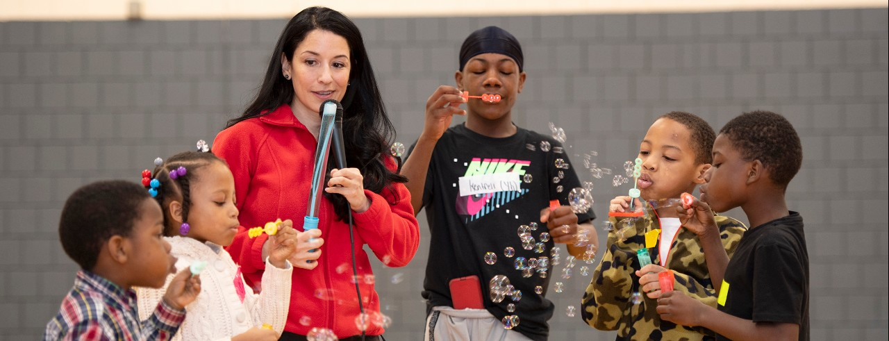 Maria Espinola seen with children blowing bubbles.