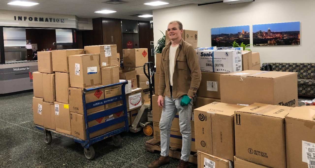 Jack Hinders stands amid boxes of donations to UC Health