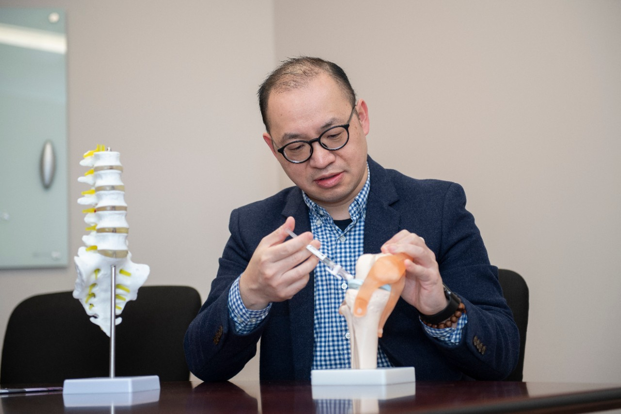 a scientist injecting a needle into a model of a spine
