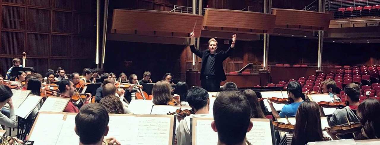A conductor leads an orchestra on stage