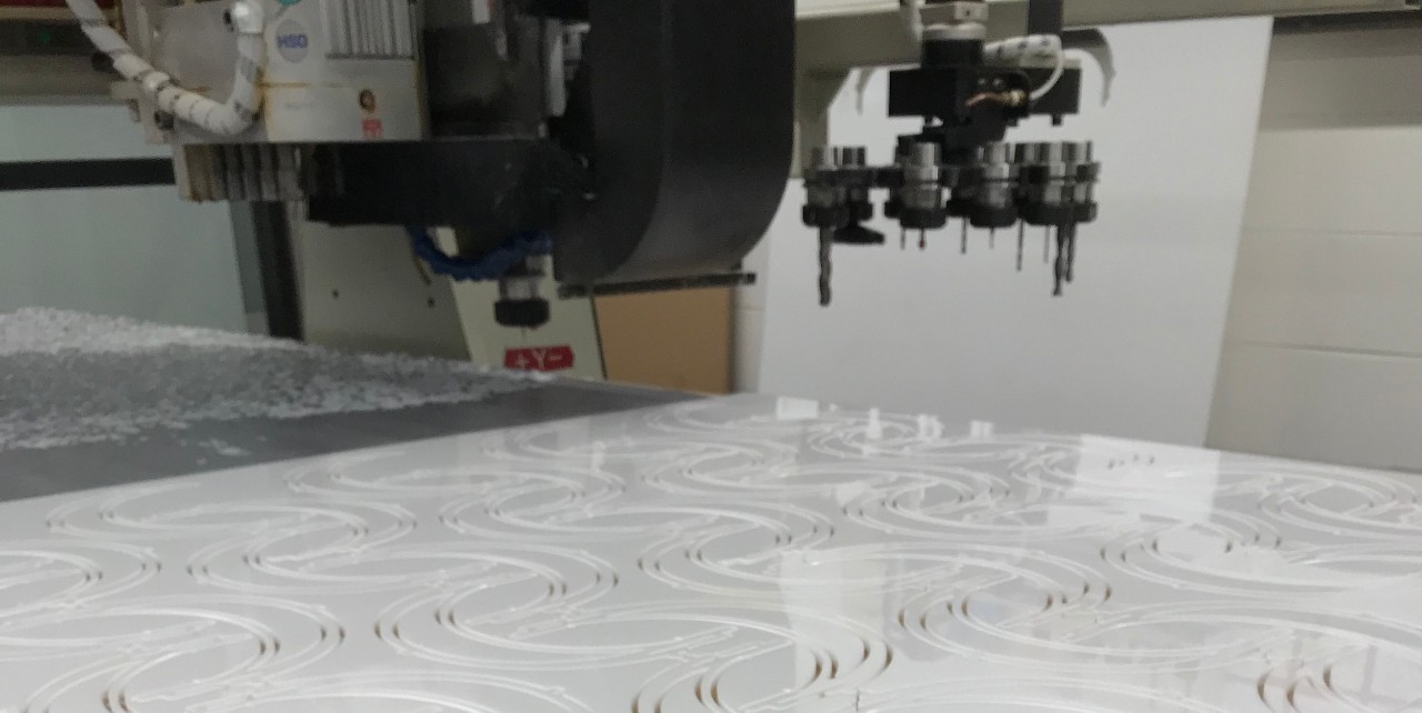 A white sheet of plastic sits atop the bed of a large robotic laser cutter