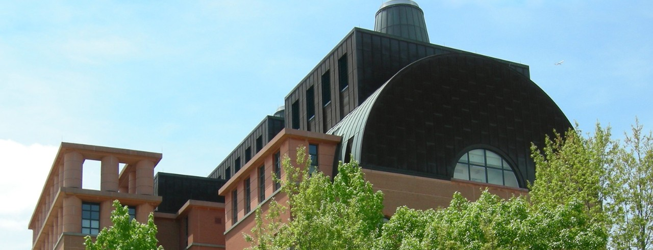a view of the top floor of the engineering research center from the ground level during the day, with treetops in the foreground