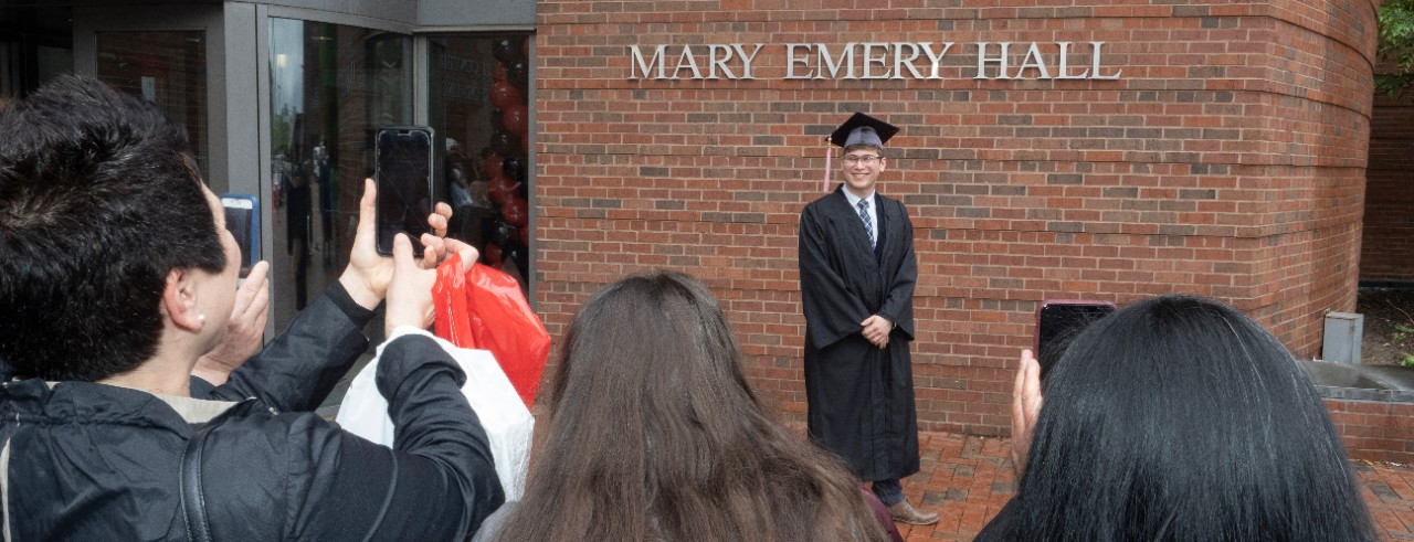 Families take pictures of their graduates in front of the CCM building