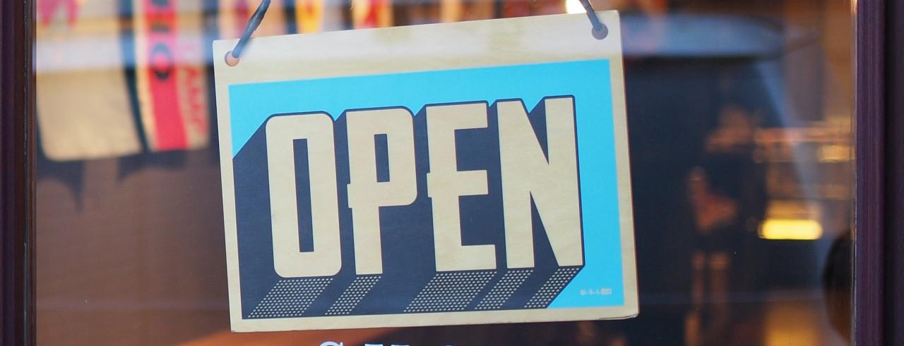 Open sign on business front glass door.