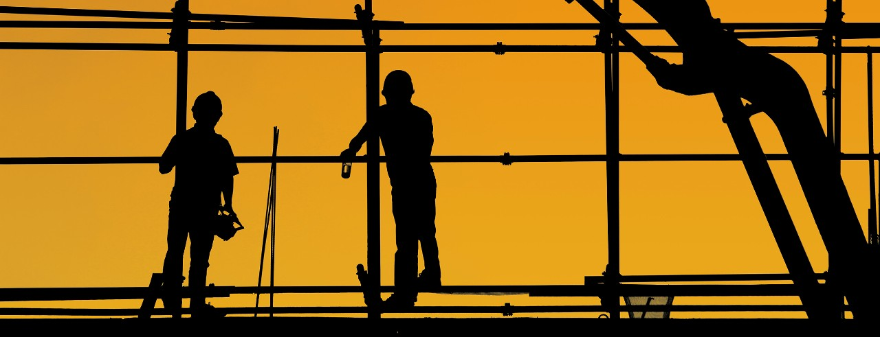 Silhoutte of two construbtion workers up high next to a machine
