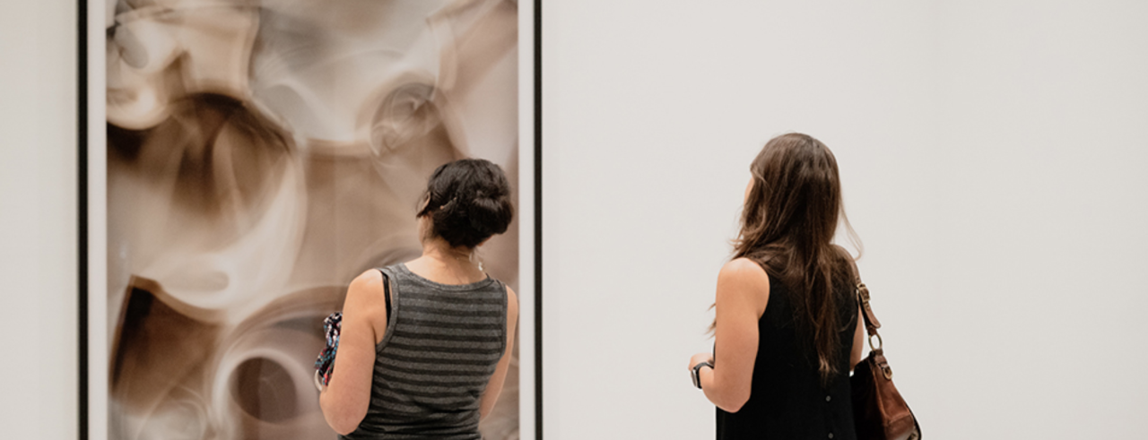 Two women look at a photograph in a gallery