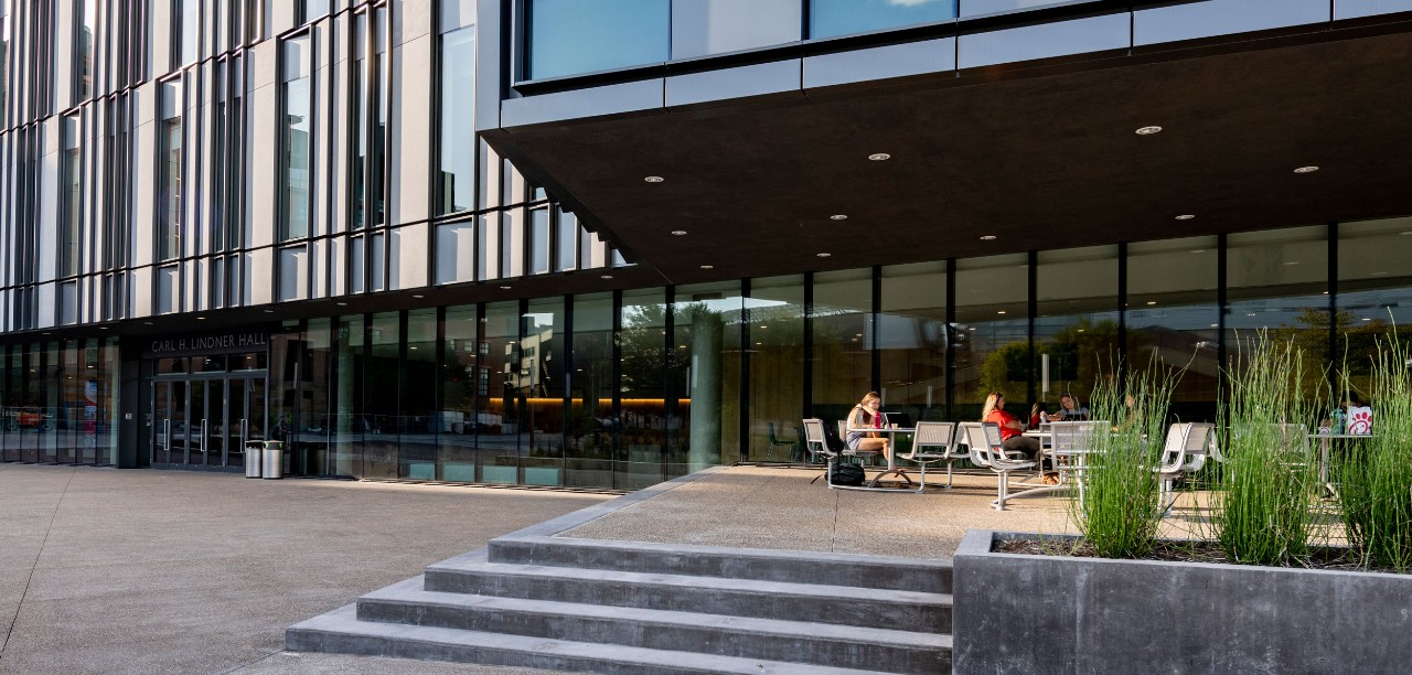 Two students sit working at a table outside the south entrance of Carl H. Lindner Hall in late afternoon/early evening. Green outdoor plants and steps are in the foreground