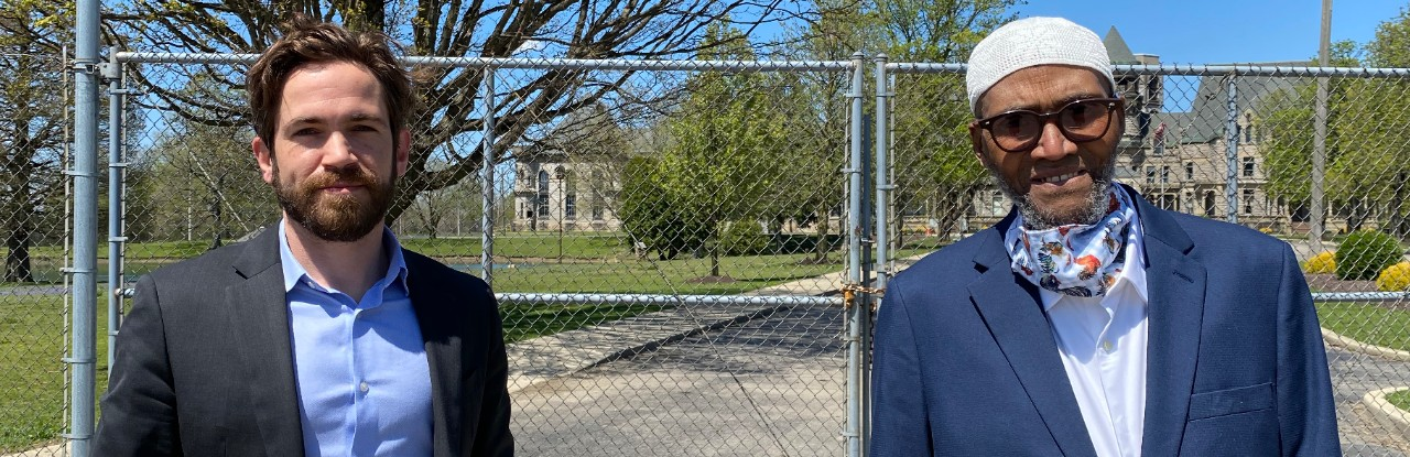 Two men in suits stand in front of a large metal gate