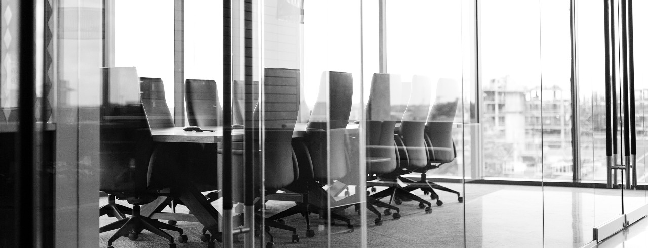 Empty corporate conference room with glass wall in high rise office building.