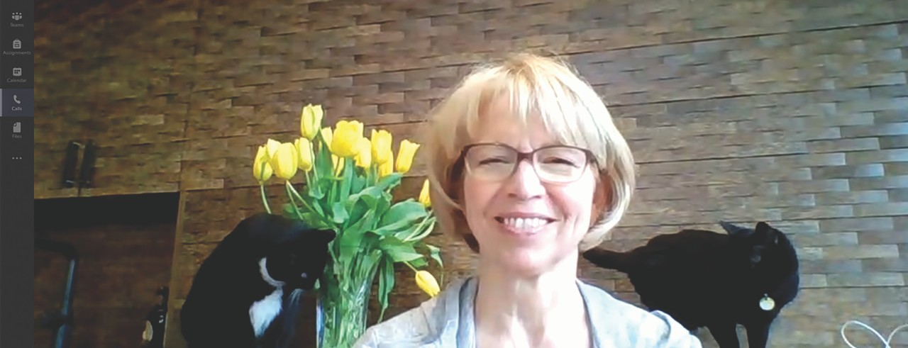 Carol Butler on a video call smiling with her two cats and yellow flowers in background.