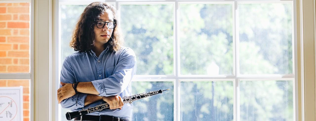 Leo De La Cruz stands with his oboe in front of a window
