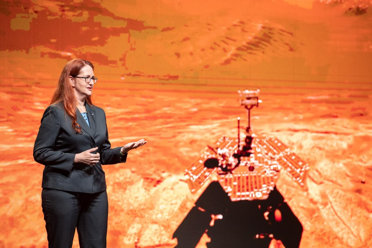 UC graduate Melissa McGuire stands on stage in front of a screen projecting the Mars rover.
