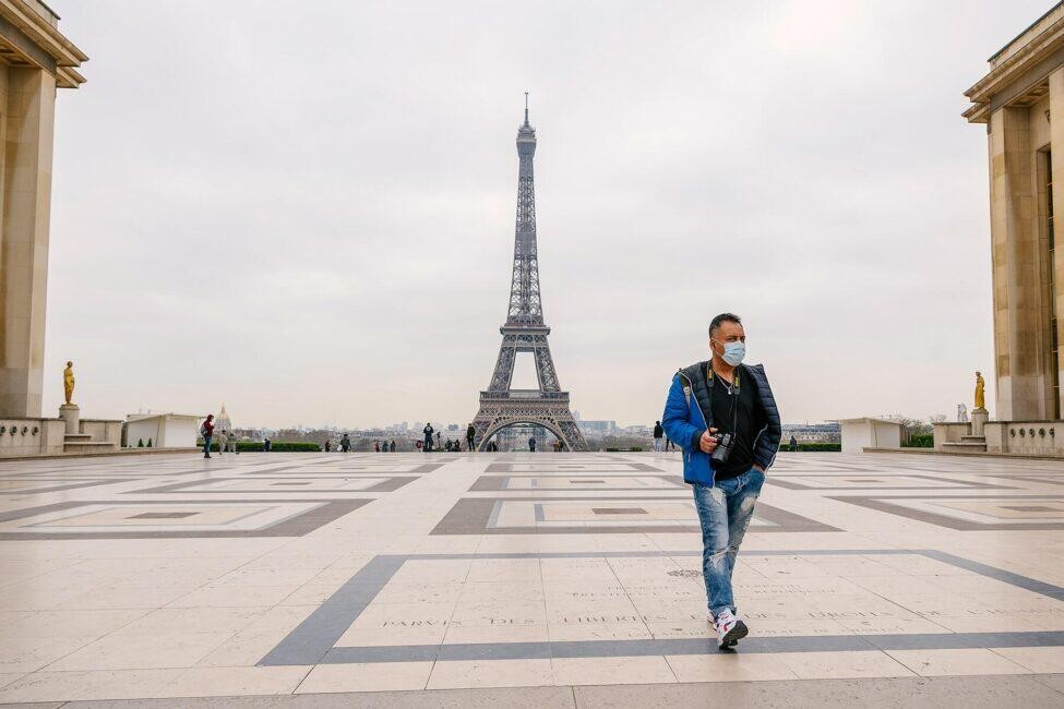 A man walks through a deserted Trocadero Square in Paris wearing a medical mask