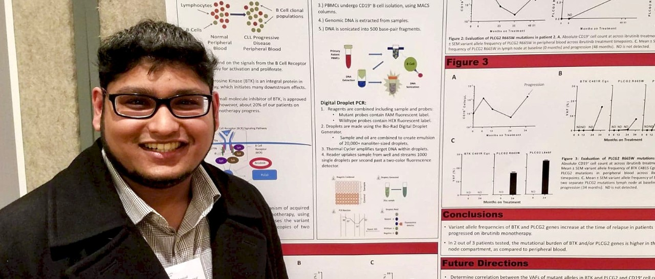 UC grad student Dylan David stands next to a poster at a scientific conference.