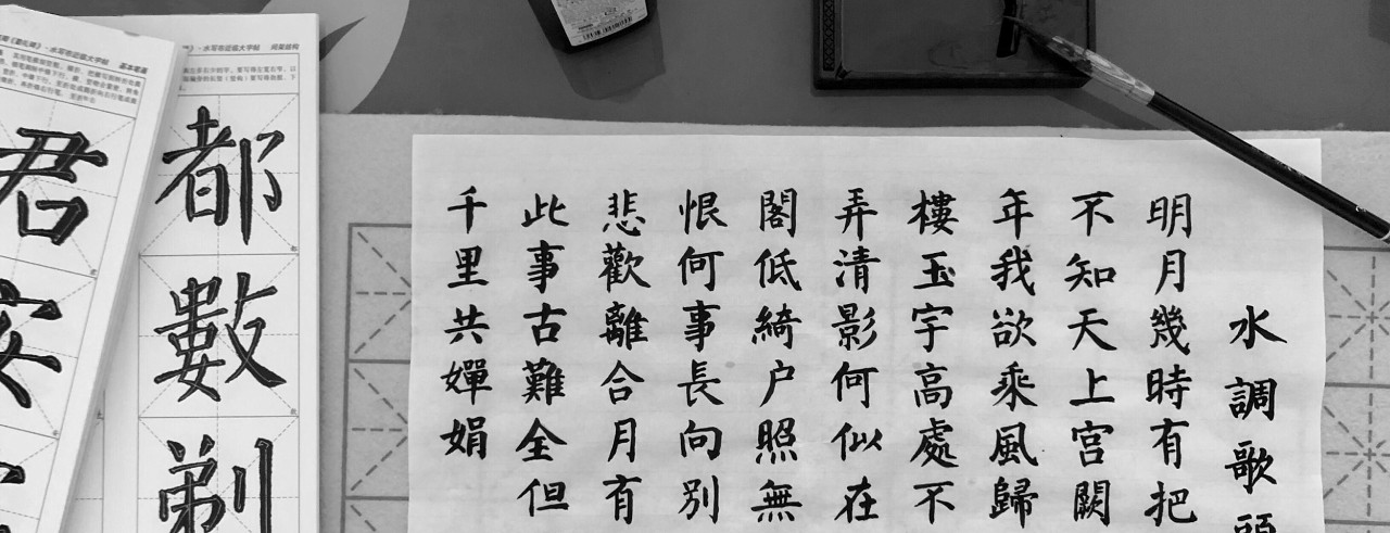 Dozens of Chinese characters on a piece of paper, with a brush and ink on table.
