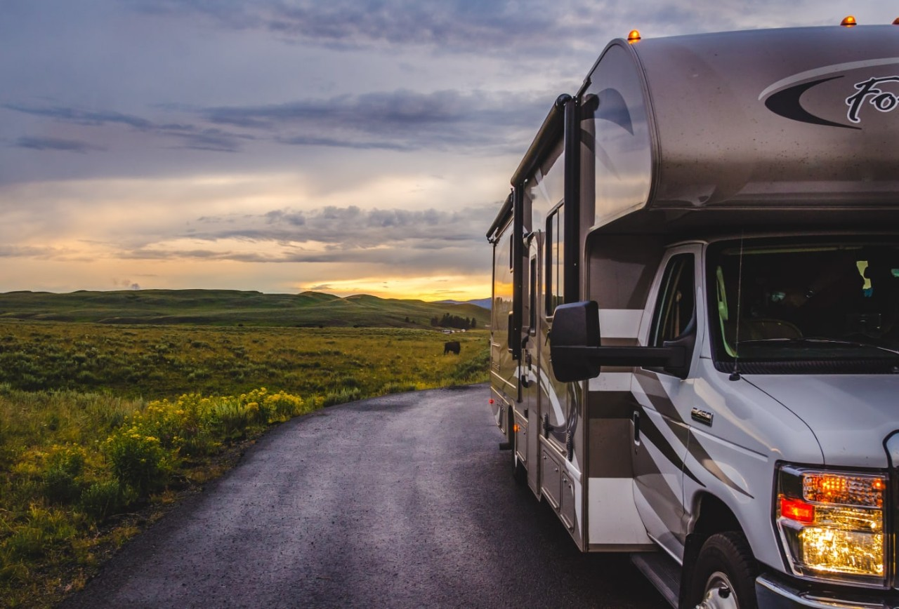 A recreational vehicle on a rural road with a sunset in the background
