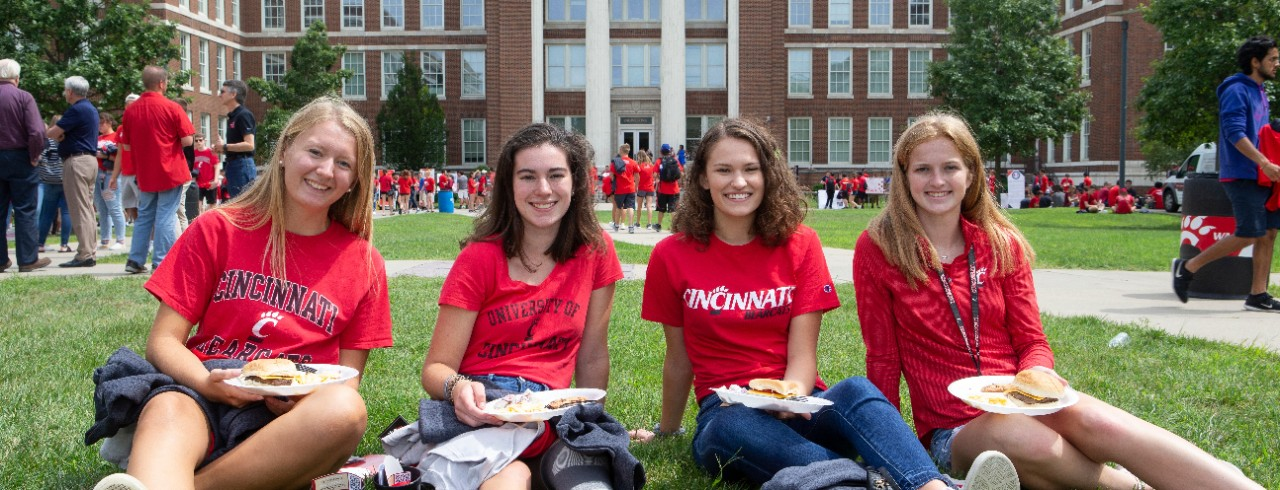 Four students sitting in the grass in front of Baldwin Hall at UC