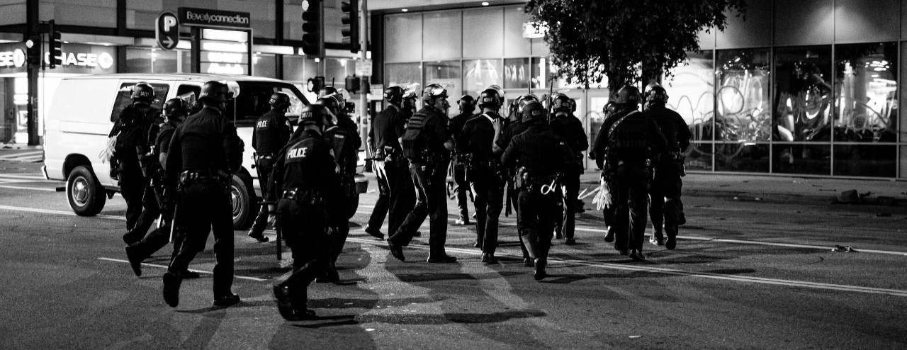 Police in riot gear respond to enforce a curfew.