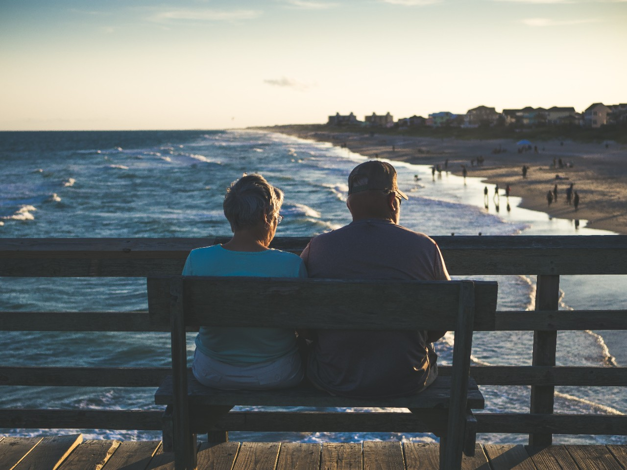 Elderly womand and man, couple, sitting on bench looking out at beach on pier.