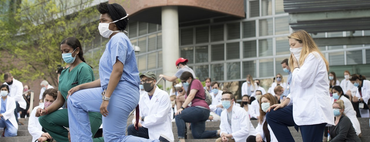 several protest kneel in front of UC College of Medicine