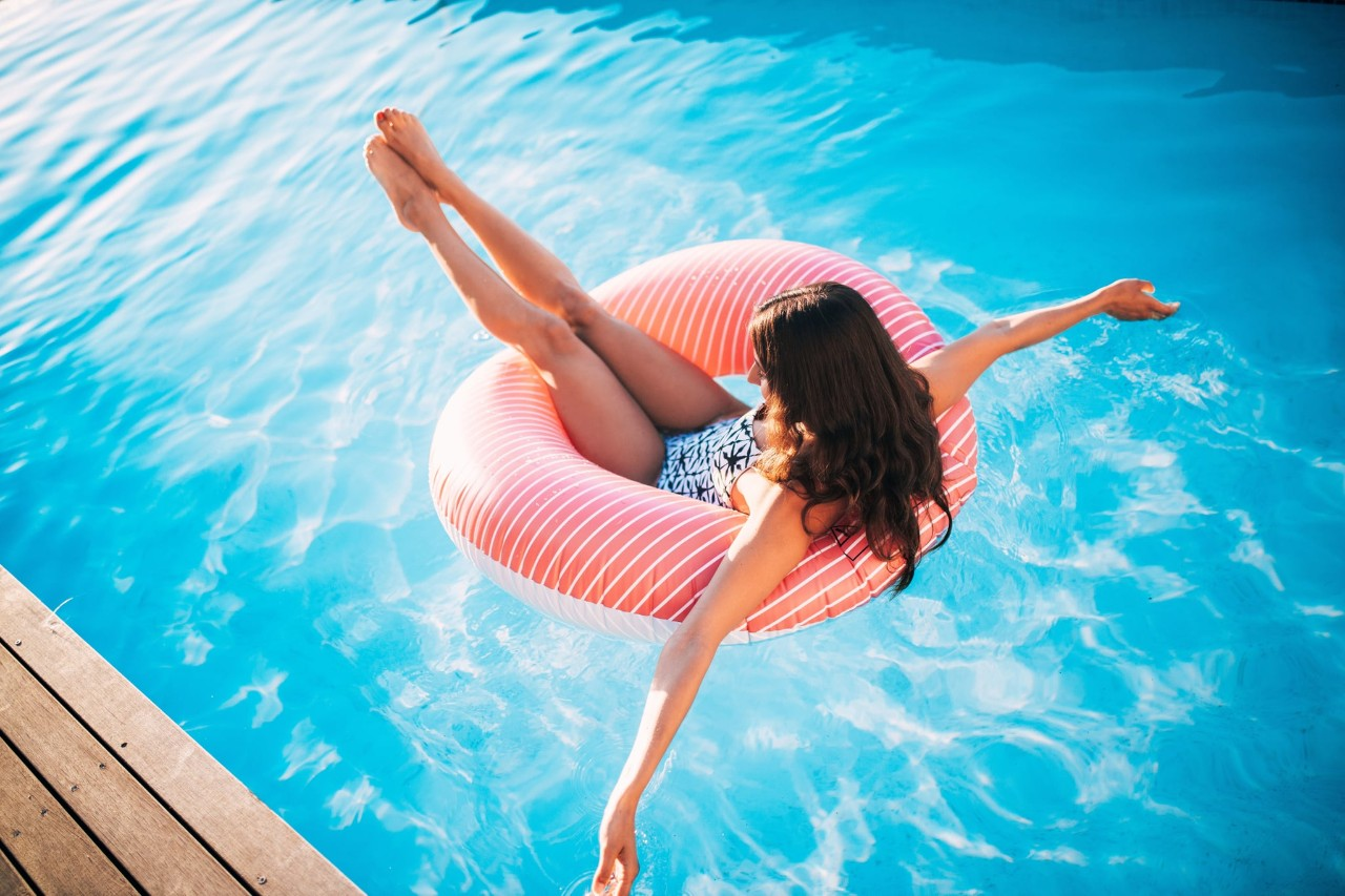 A woman laying in an inner tube in a swimming pool